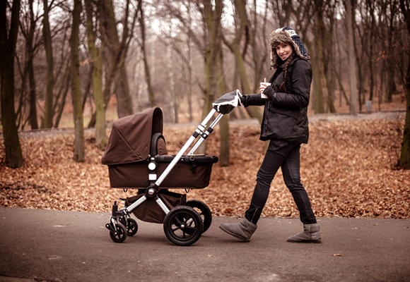 Young stylish mother walking in the fall  park with stroller